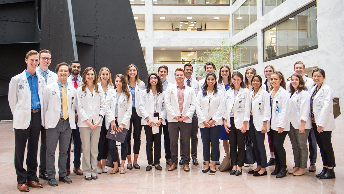 A group of medical students stand together for a group photo in a congressional building on Capitol Hill