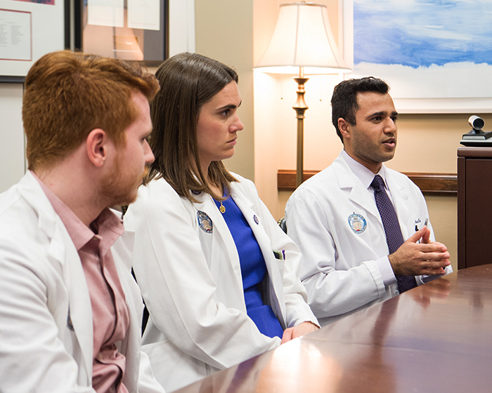 Three medical students sit at a table in a congressional office