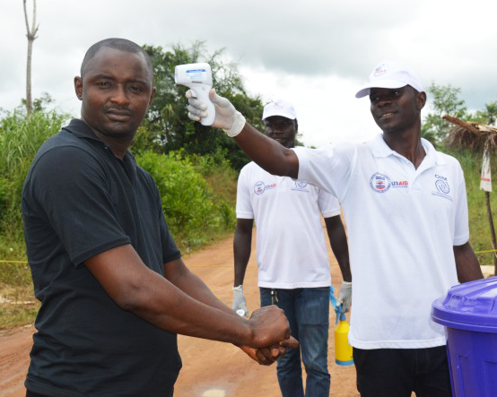 A man at a border crossing in Africa holds a thermometer to the forehead of another man who is washing his hands