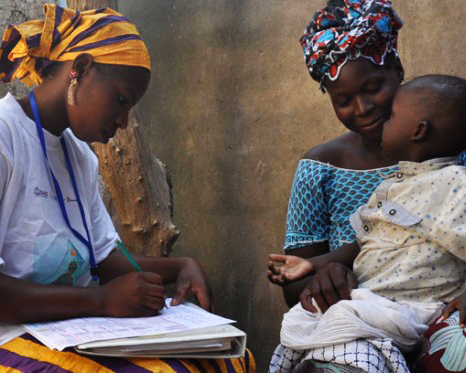 A woman writes out a health record as another woman holds a child on her lap
