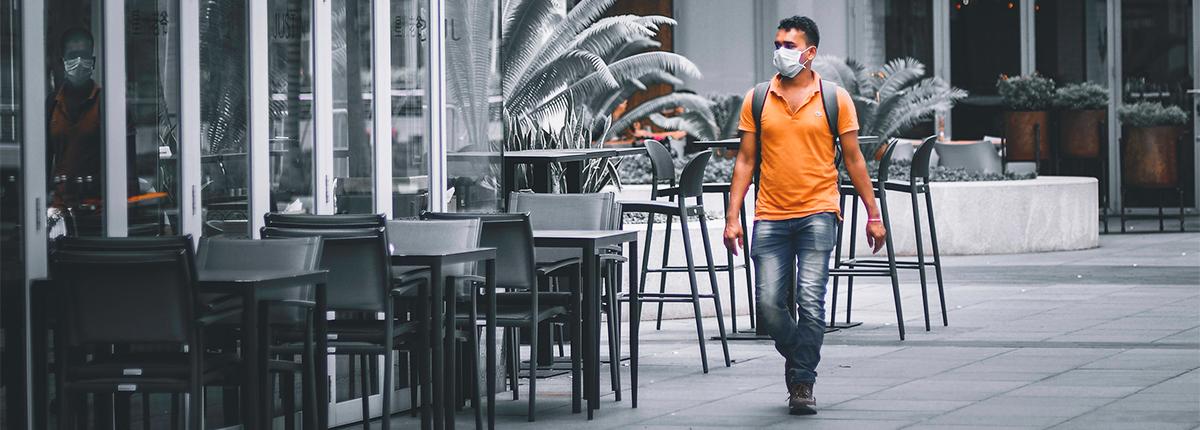 A man wearing a mask walks an empty street