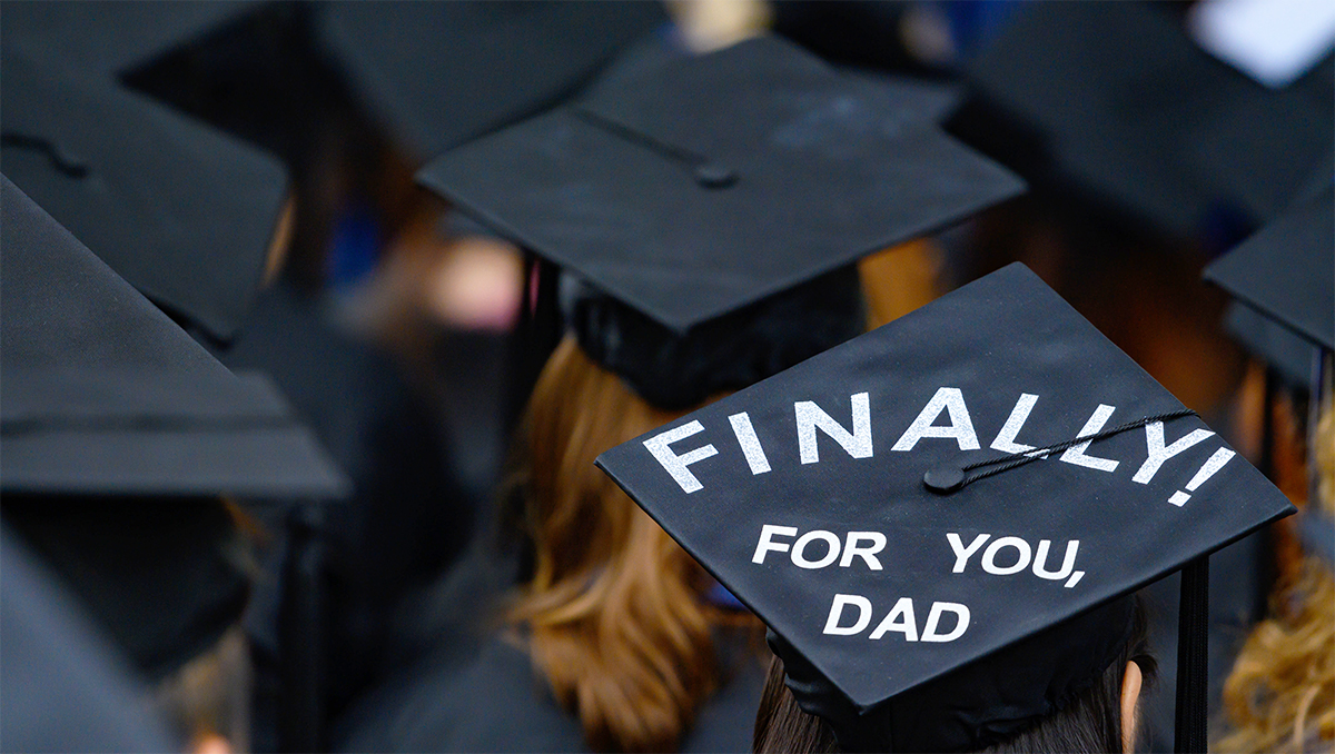 "Students at graduation wear mortarboards, one emblazoned with the message ""Finally, For you Dad!"""