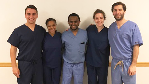 A group of medical students in scrubs stand together for a group photo