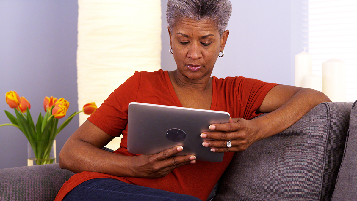 A woman sits on a couch looking intently at a tablet in her hands