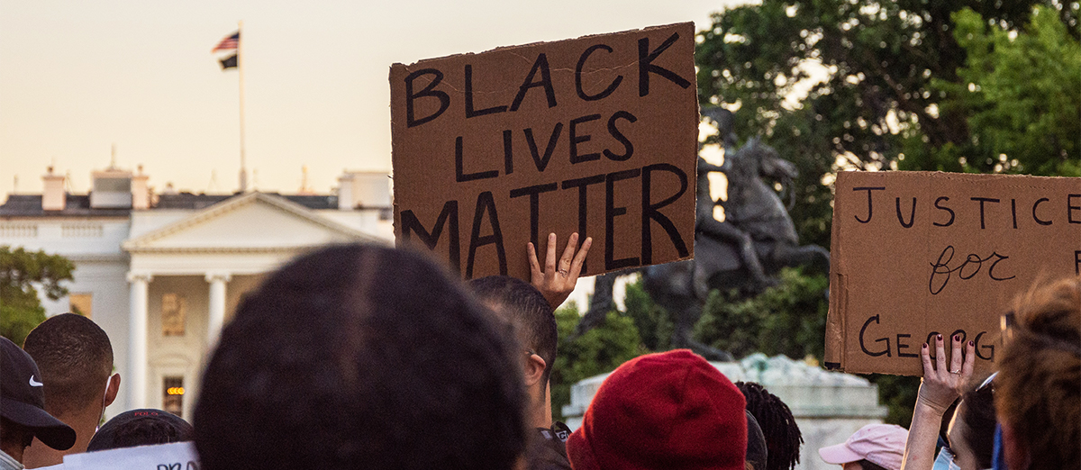 Protestors hold up signs outside the White House that say 'Black Lives Matter'