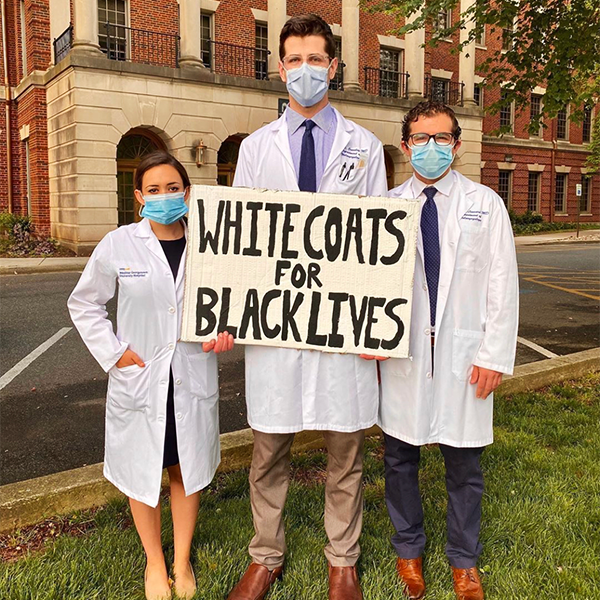 Three medical students in white coats stand together wearing masks and holding a sign that says White Coats for Black Lives