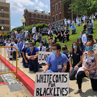A large group of medical professionals participate in a protest outside MedStar Georgetown University Hospital