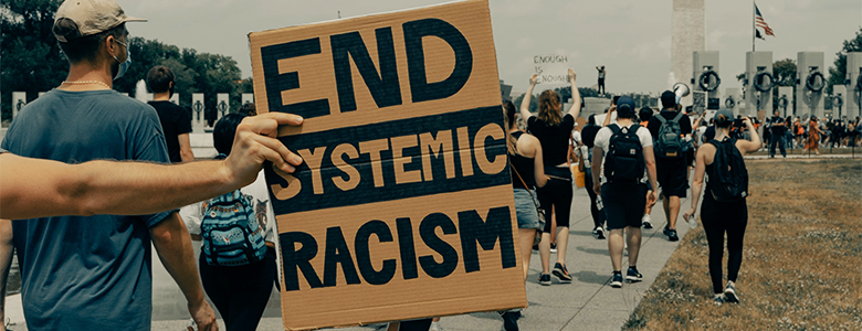 Protestors walk near the Washington Monument, one holding a sign that reads End Systemic Racism
