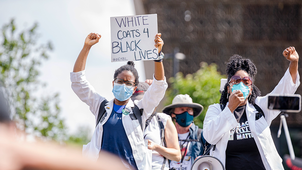 A group of medical students wearing white coats and surgical masks participate in the White Coats for Black Lives protest.