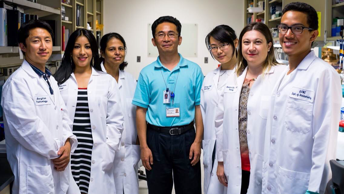 A group of people, most wearing white lab coats, stand together in a lab