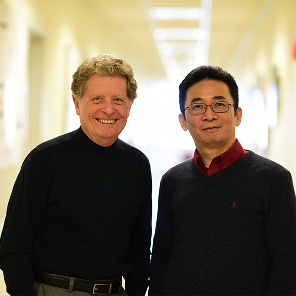Richard Schlegel and Xiufeng Liu stand in a hallway