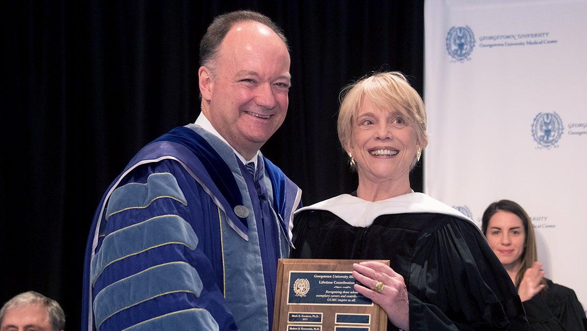 Jack DeGioia hands Victoria Jennings a plaque at Convocation 2016