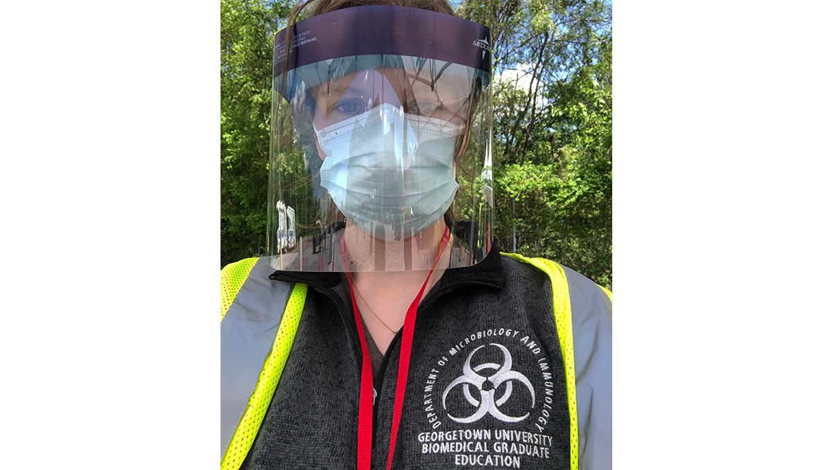 Suzie Stephenson in full personal protective equipment wearing a shirt with the Biomedical Graduate Education logo