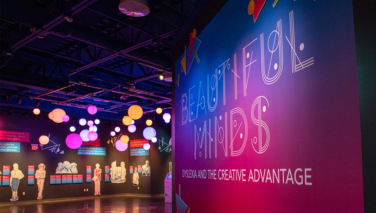 """A wall in a museum exhibit says """"Beautiful Minds, Dyslexia and the Creative Advantage, """" behind it can be seen glowing shapes in the exhibit space"""