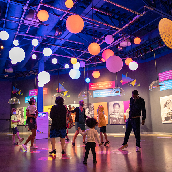 Children and adults dance beneath the glowing orbs of the museum exhibit