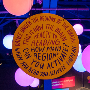 """A sign explains how the interactive exhibit works: """"Dance under the regions of the brain. This is how the brain reacts to reading. How many regions can you activate? When you read you activate them all."""""""