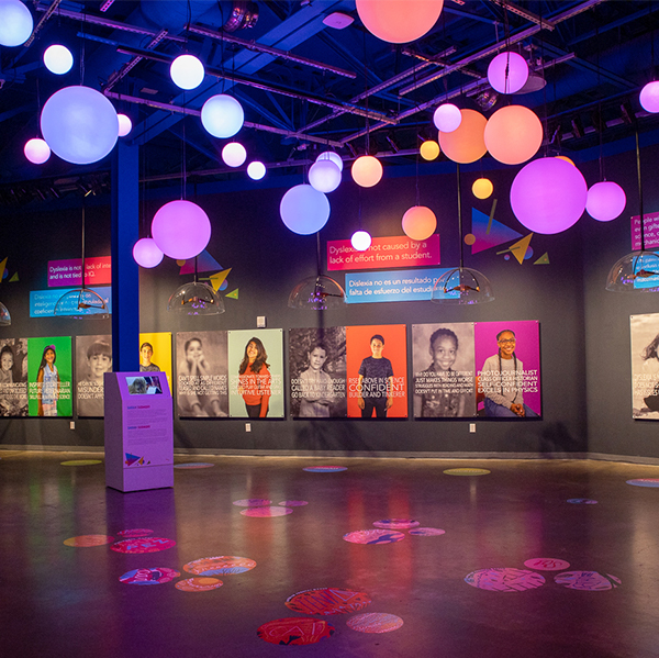 A museum exhibit space is filled with glowing orbs suspended from the ceiling