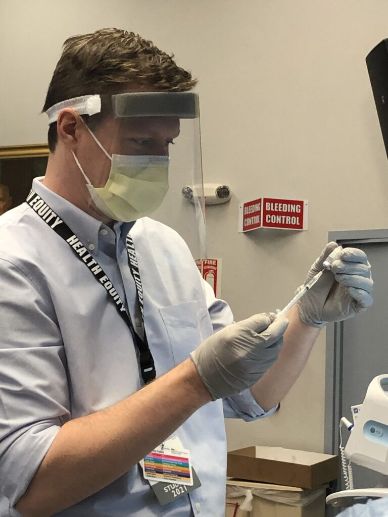 Stephen Kane wears a mask and gloves to prepare a dose of the vaccine in a clinical setting