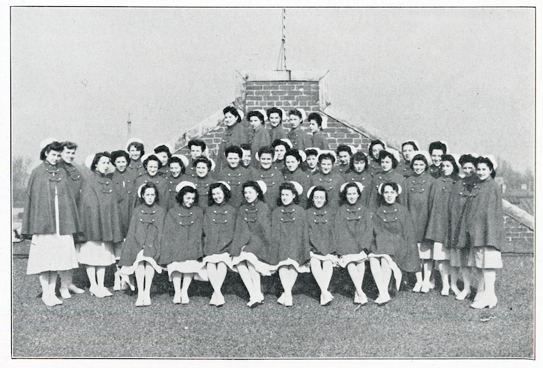 A historical image of a large group of nursing students standing outdoors in their uniforms