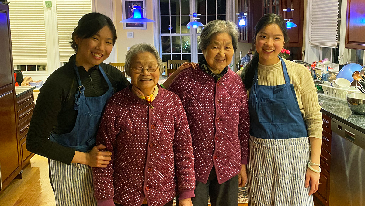 Four women stand in a home kitchen
