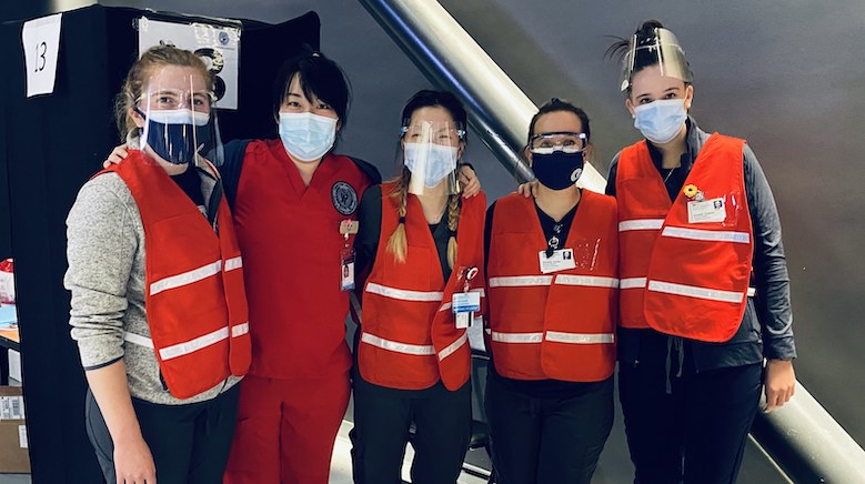 Students stand side by side dressed in clinical PPE