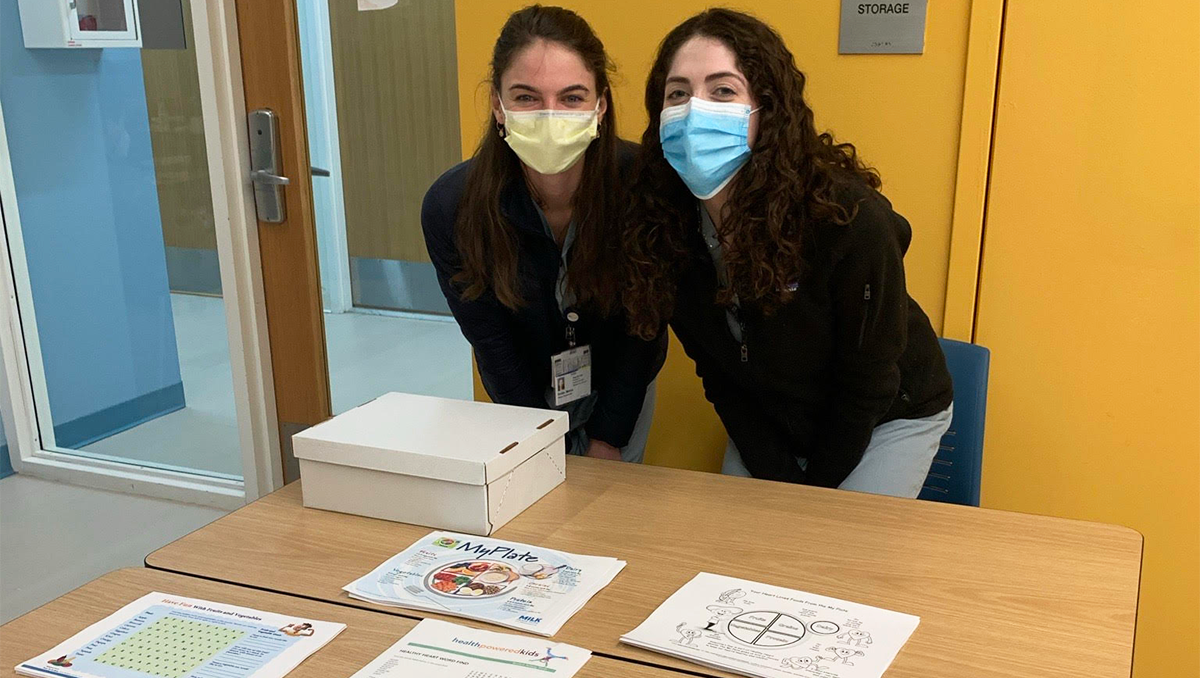Two students wearing masks stand side by side behind a table filled with paper fliers