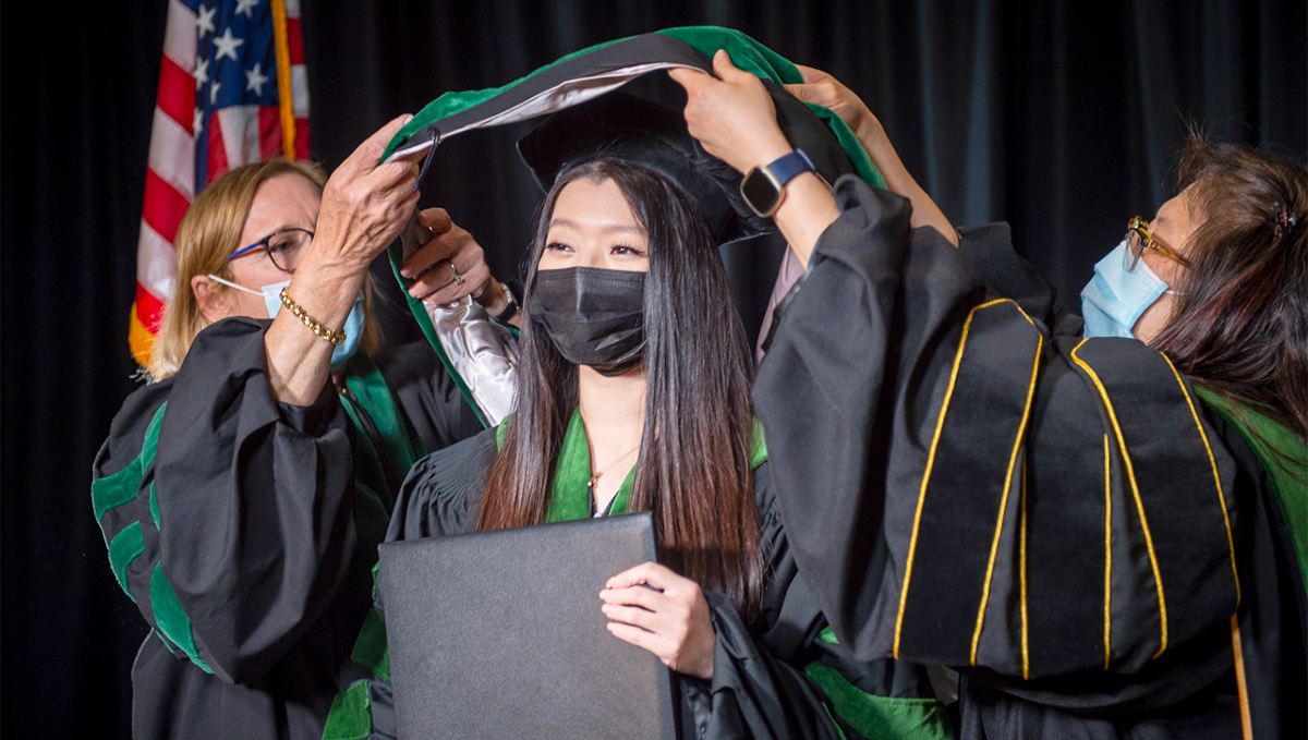 Two women lift a ceremonial hood over the shoulders of a third woman in academic regalia