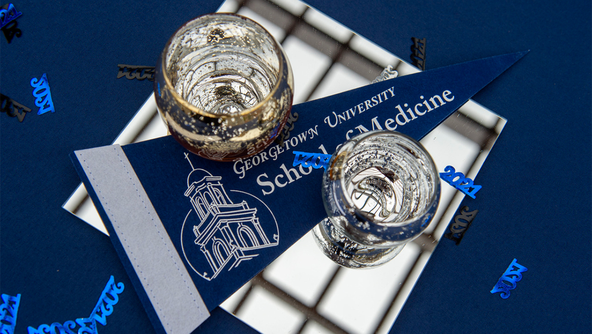 A centerpiece from the commencement parties hosted by the School of Medicine displays a school pennant atop a glass square with two candleholders on either side