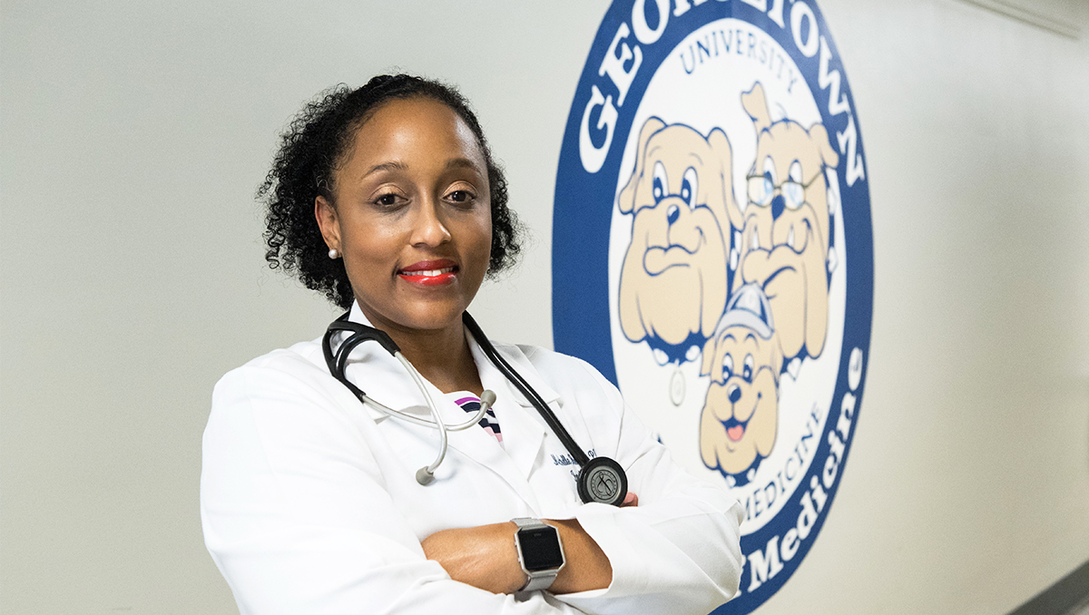 Dr. Michelle Roett stands in a hallway at GUSOM next to a mural of the Department of Family Medicine logo