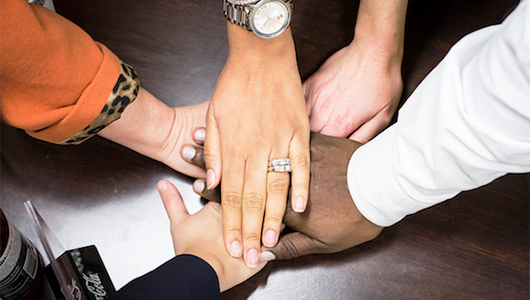 People put their hands featuring different skin tones together on a table in a show of solidarity