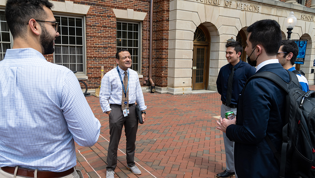 Lee Jones speaks with three medical students outdoors on campus