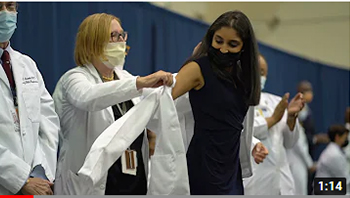 Thumbnail of video for White Coat ceremony featuring a professor helping a student put on a white coat