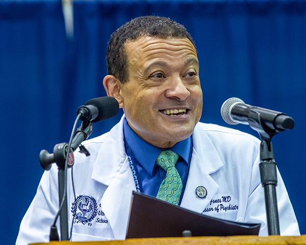 Dean Jones speaks at a podium during White Coat