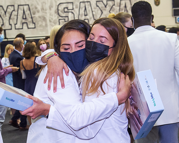 Two female medical students hug following the White Coat ceremony