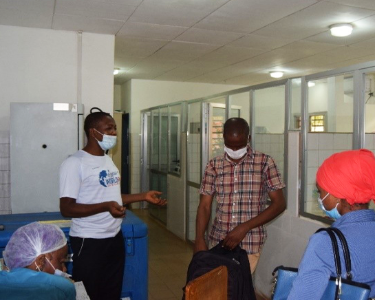 Four people wearing protective masks have a discussion in a hospital hallway