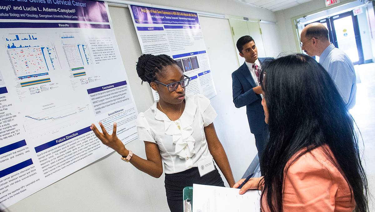 A student gestures toward a poster on the wall while speaking with a professor
