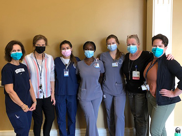 A group of medical professionals stand together in a line