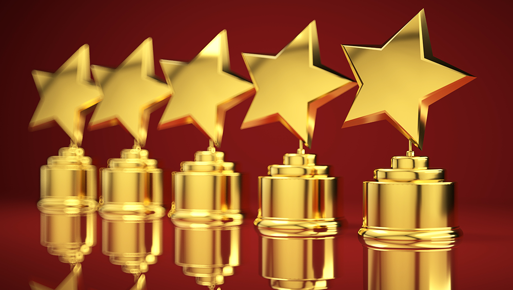 Photoillustration of star shaped awards in a row against a red background